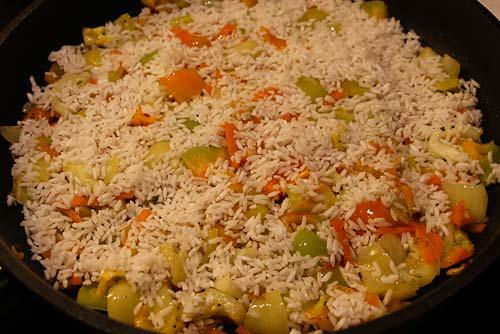 Добавить рис и обжарить помешивая