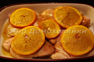 Апельсины уложить на куски курицы и запечь в духовке