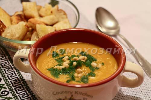 Подавать тыквенный крем-суп с сухариками и орешками